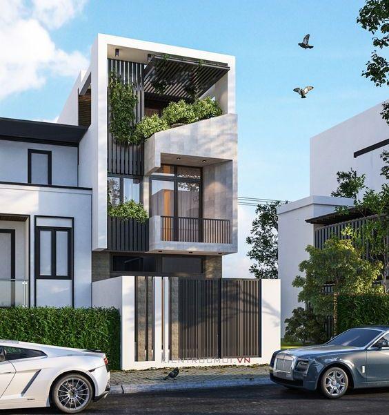 Thiết kế nhà phố 3 tầng có cổng sắt đơn giản, mặt đứng sử dụng lam chắn nắng, ban công sắt đơn giản hiện đại. Có trồng cây xanh xen kẽ