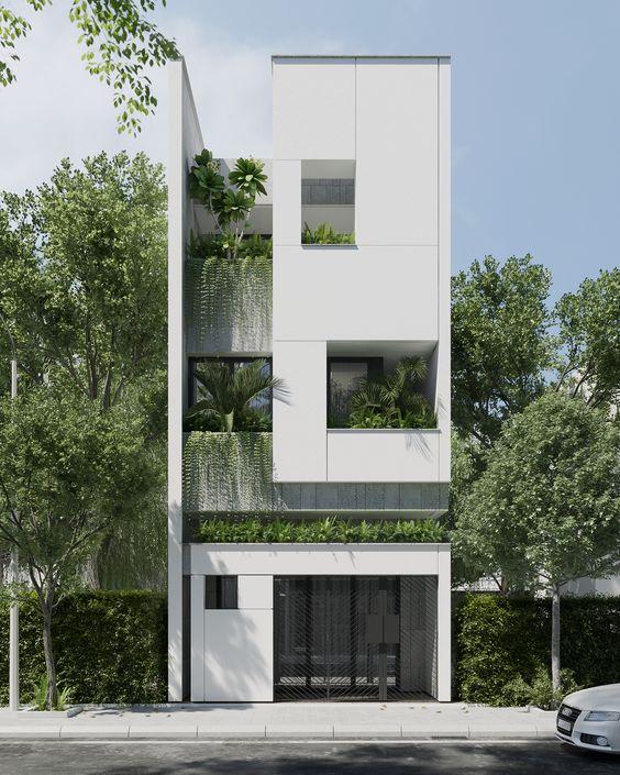 Mẫu nhà phố 3 tầng sử dụng các lỗ vuông trang trí trên nền phẳng màu trắng. Liên thông khối giữa các tầng khá rõ ràng phá đi cảm giác về số tầng theo cách truyền thống. Cây xanh mặt tiền mang lại hiệu ứng cặp màu sắc xanh trắng rõ ràng