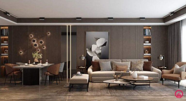 Phòng khách liền kề phòng ăn có bộ bàn ăn, vách ốp gỗ, tranh treo phòng khách, tủ âm tường, sofa nỉ màu be, bàn trà kép thấp mặt đá nhân tạo, ghế sofa đơn có thảm và lát gạch sàn, rèm và cửa nhôm kính