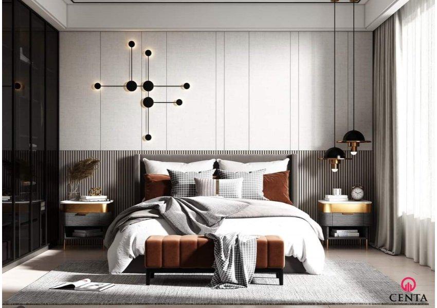 Phòng ngủ có vách ốp đầu giường nan gỗ và ốp nỉ trắng. Đèn thả trang trí, rèm xám trắng
