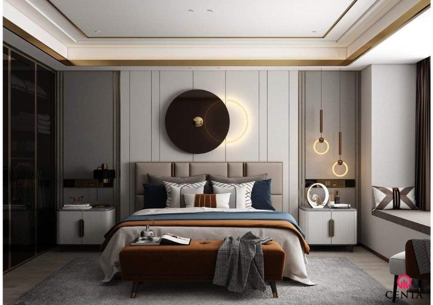Phòng ngủ có giường bọc đầu giường bằng nỉ, giường con, 2 táp đầu giường màu trắng, ốp vách nỉ màu be và đèn trang trí